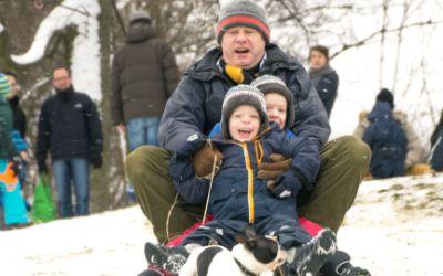 Vater mit seinen beiden Kindern beim Rodeln