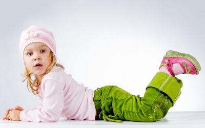 Liegendes kleines Mädchen mit rosa Mütze und grüner Hose