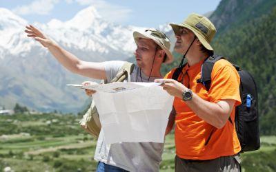 Zwei Männer beim Wandern mit einer Karte in den Bergen.