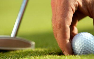 Golfspieler positioniert den Ball auf dem Grün