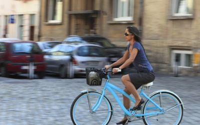 Frau auf blauem Fahrrad fährt durch die Stadt im Sommer.
