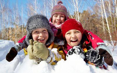 Kinder lachen liegend im Schnee