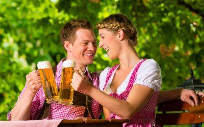 Pärchen stößt im Biergarten mit Bier an