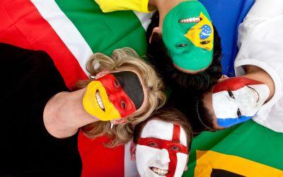 Vier Fans verschiedener Nationalitäten haben die Flaggen ins Gesicht geschminkt