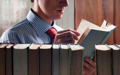 Mann liest hinter Bücherregal