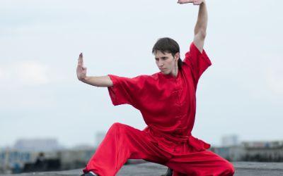 Kung Fu Kämpfer übt im roten Anzug