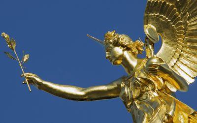 Der goldene Friedensengel in München vor blauem Himmel,