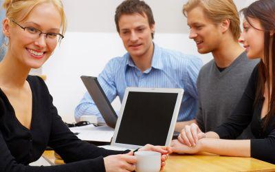 Zwei Männer und zwei Frauen an einem Bürotisch