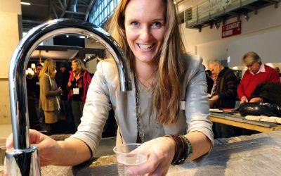 Eine Frau schenkt sich auf der Messe Heim+Handwerk in München ein Glas Wasser ein.