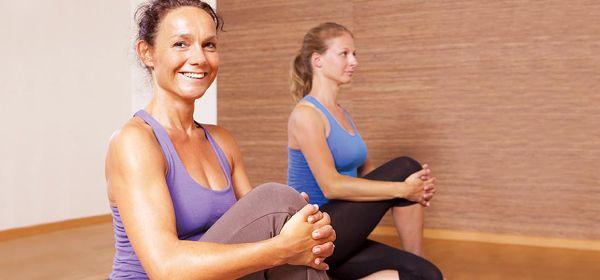 Zwei Frauen beim Stretching auf Sportmatten