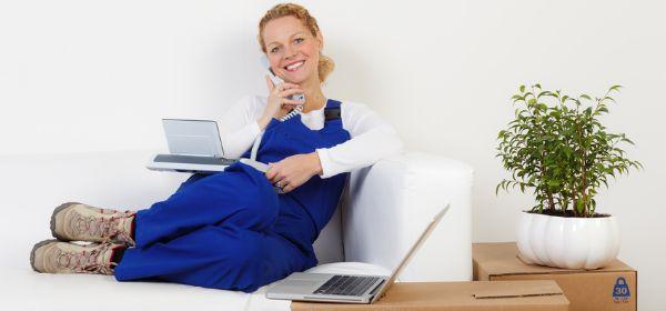 Frau beim Umzug mit Telefon und Laptop auf der Couch