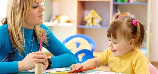 Frau sitzt mit Mädchen am Tisch, das malt