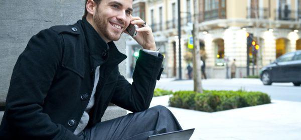 Mann auf Treppe mit Handy und Laptop