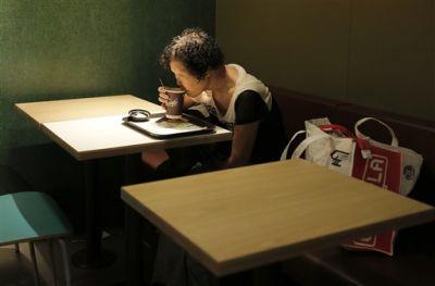 Mary Seow bebe café el viernes 20 de noviembre de 2015 en un establecimiento 24 horas de McDonald's en donde comenzó a dormir hace unas cuatro semanas después de enterarse que otros hacían lo mismo en Hong Kong. La mujer de Singapur que desapareció hace casi cinco años se ha reunido con su hijo después de que un artículo de Associated Press sobre personas que duermen en establecimientos 24 horas de McDonald's en Hong Kong recogiera su difícil situación. (Foto AP/Vincent Yu)