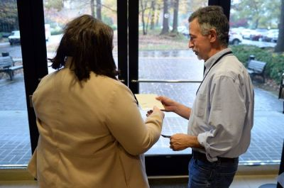 El especialista de informática del AJC, John Perry le entrega el CD con información de 6 millones de votantes a una investigadora de la secretaría de estado, el miércoles 18 de noviembre pasado. Foto: Kent D. Johnson/AJC