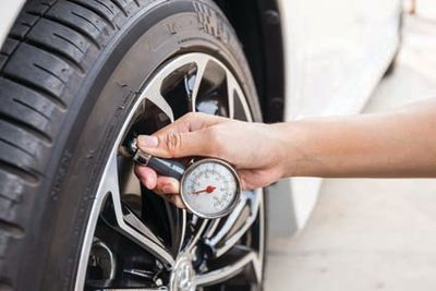 Close-Up Of Hand holding pressure gauge for car tyre pressure me