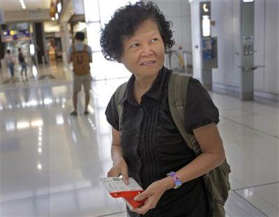 Mary Seow sostiene una tarjeta de embarque tras ponerse en contacto con su hijo, que aparece al fondo con mochila, en el aeropuerto de Hong Kong, el sábado 21 de noviembre de 2015. (AP Foto/Vincent Yu)