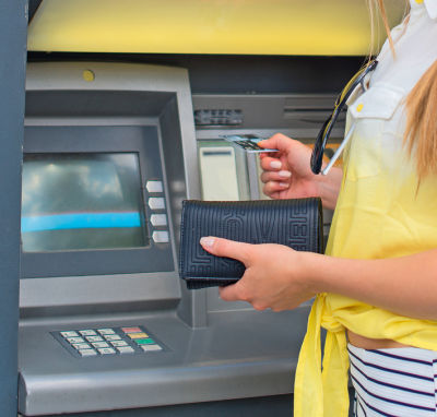 Withdrawing money from an ATM. Unrecognizable person.