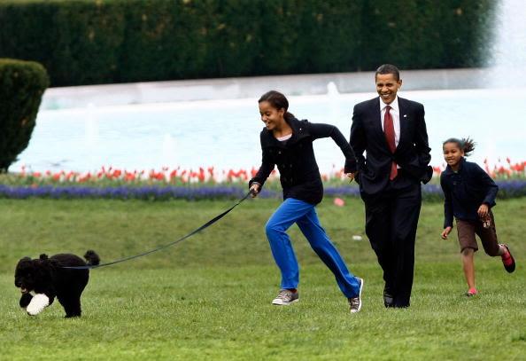 Malia (izquierda) y Sasha acompañan a su padre a pasear al perro de la familia, Bo, el 14 de abril de 2009. Foto: Getty Images.