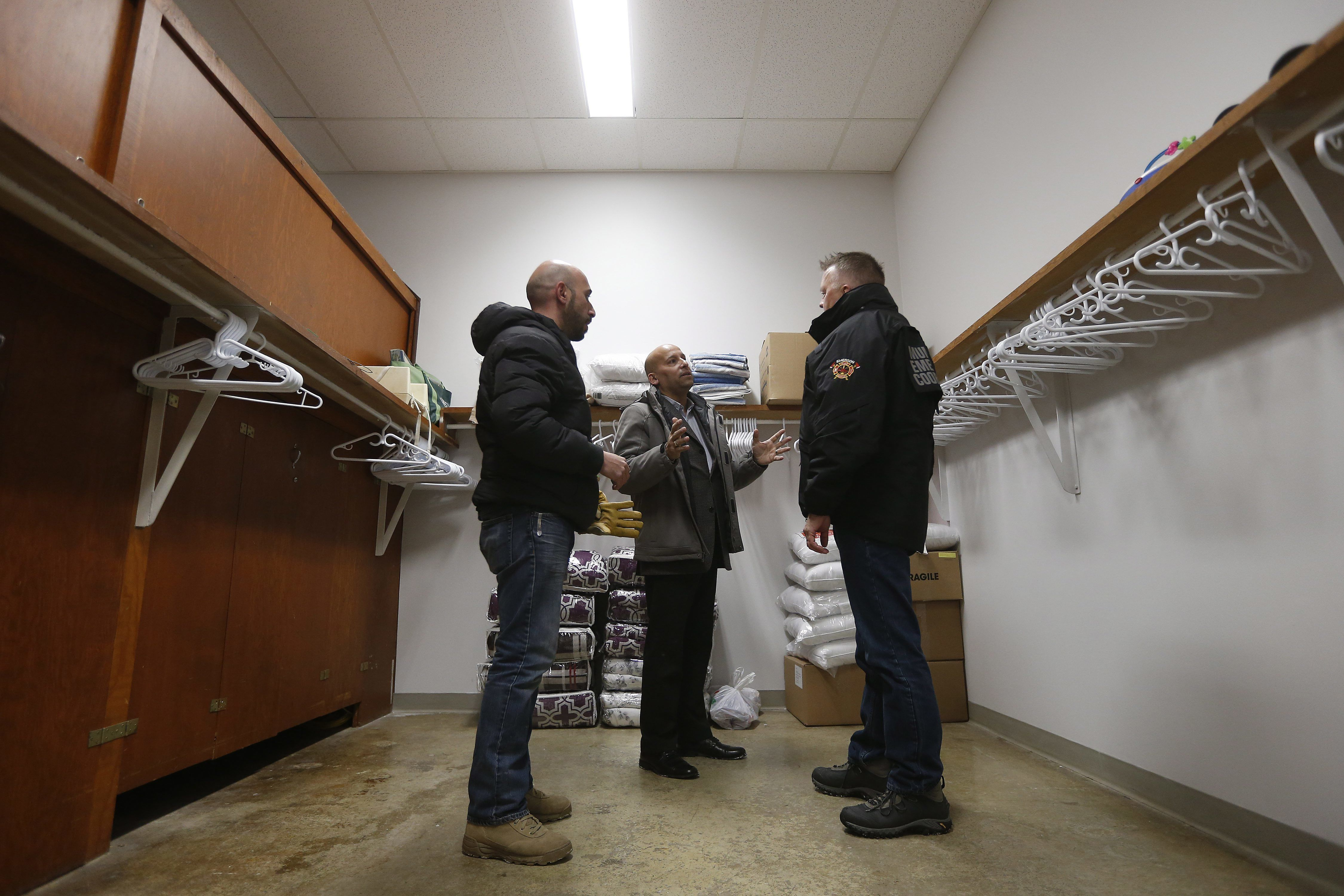 From left, Fadel Alshawwa, Jean Pierre Venegas, Manager of the Manitoba Interfaith Immigration Council, and Bill Spanjer, Municipal Emergency Coordinator for Emerson-Franklin bring blankets and pillows into a community hall for refugees that may walk across the border in Emerson, Manitoba, Thursday, Feb. 9, 2016. Refugees have been crossing into Canada at Emerson and authorities had a town hall meeting in Emerson to discuss their options. (John Woods/The Canadian Press via AP)