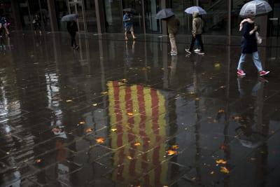 Gente caminando junto a una bandera catalana reflejada en un charco en Barcelona, España, el jueves 19 de octubre de 2017. (AP)
