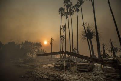 Humo se alza detrás de un complejo de apartamentos destruido por incendios forestales en Ventura, California, el martes, 5 de diciembre del 2017. FOTO: (AP)