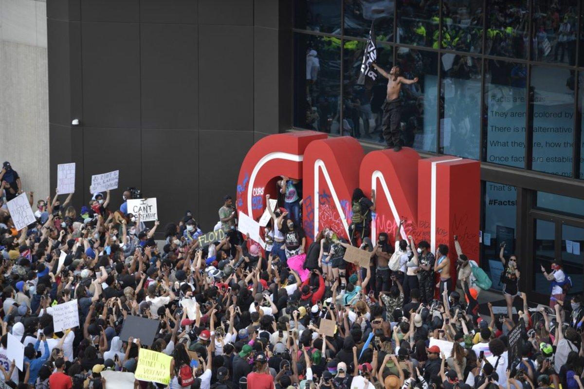 Los manifestantes pintaron en el logotipo de CNN durante una protesta en Atlanta, en respuesta a la muerte de George Floyd bajo custodia policial el Día de los Caídos en Minneapolis. La protesta comenzó pacíficamente más temprano en el día antes de que los manifestantes se enfrentaran con la policía. (Foto AP / Mike Stewart)