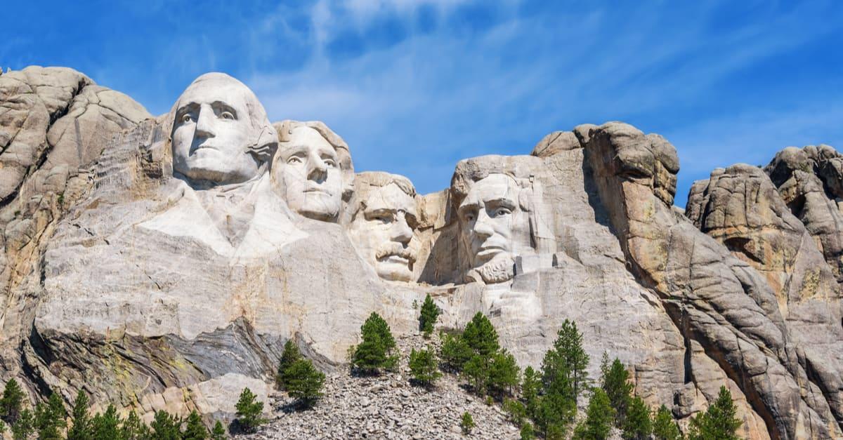 Escultura presidencial en el monumento nacional Mount Rushmore, Estados Unidos. Día soleado, cielo azul.