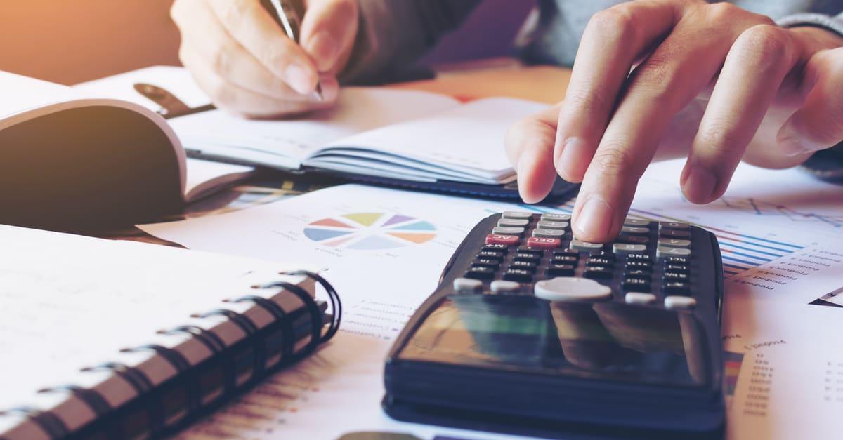 Mano haciendo finanzas y calcula en el escritorio sobre el costo en la oficina doméstica.