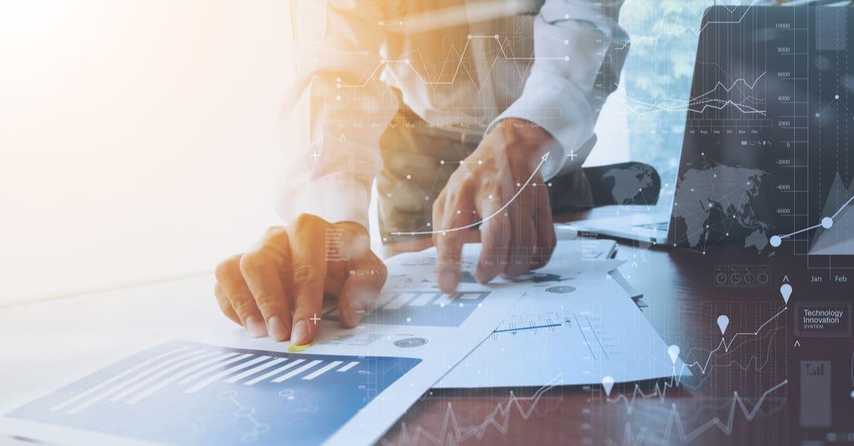 documentos comerciales en la mesa de oficina con smartphone y tableta digital y gráficos financieros con diagrama de redes sociales y el hombre trabajando en segundo plano