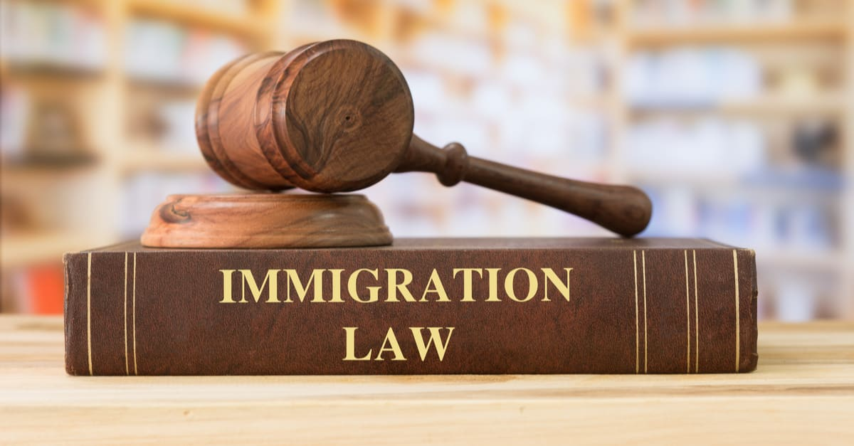 Immigration Law books with a judges gavel on desk in the library. Legal education concept.