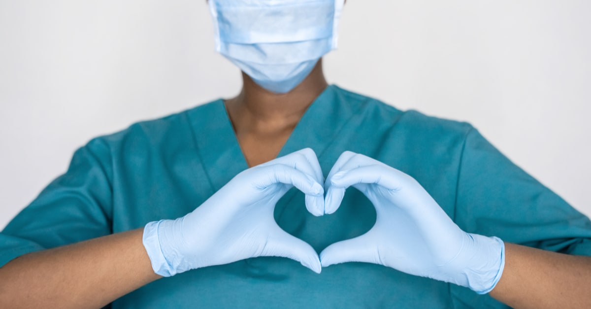 Female african professional medic nurse wear face mask, gloves, blue green uniform showing heart hands shape.