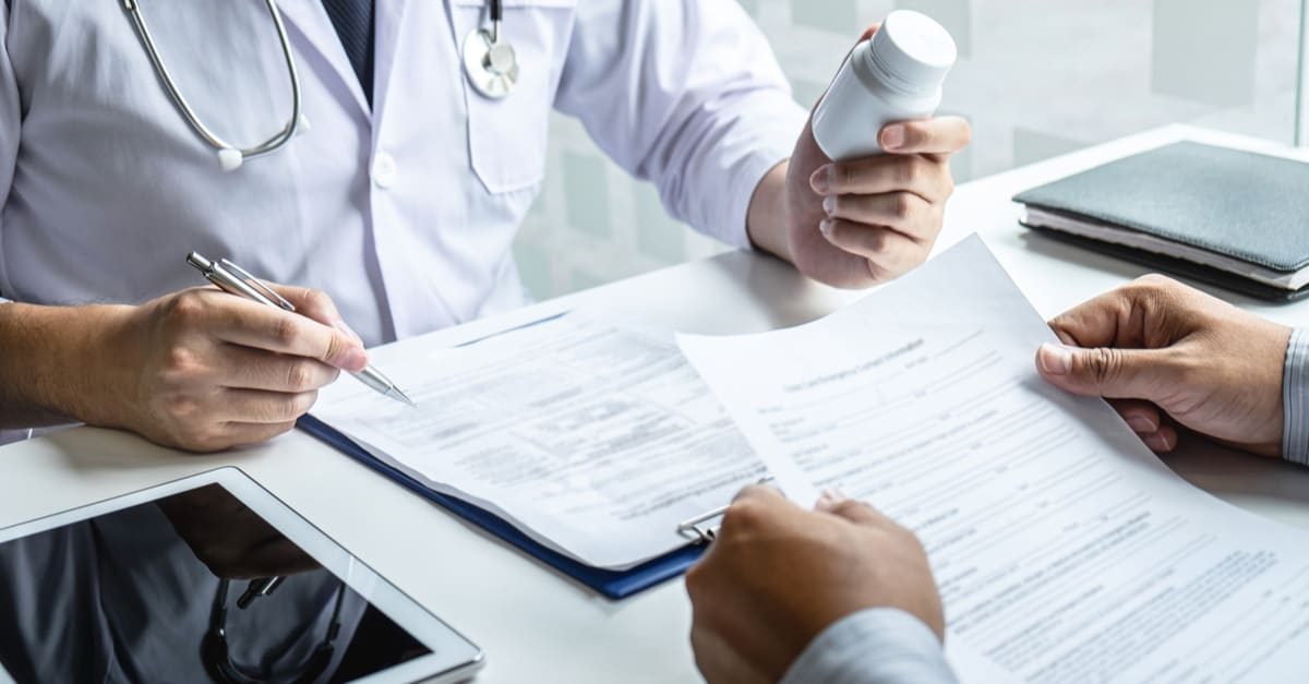 Doctor consulting with patient and checking sickness condition while presenting results diagnosis symptom