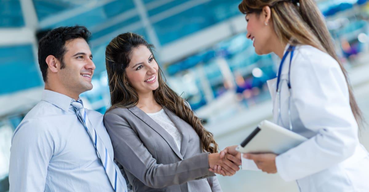 Seguro estados unidos medico Doctor handshaking with a couple at the hospital