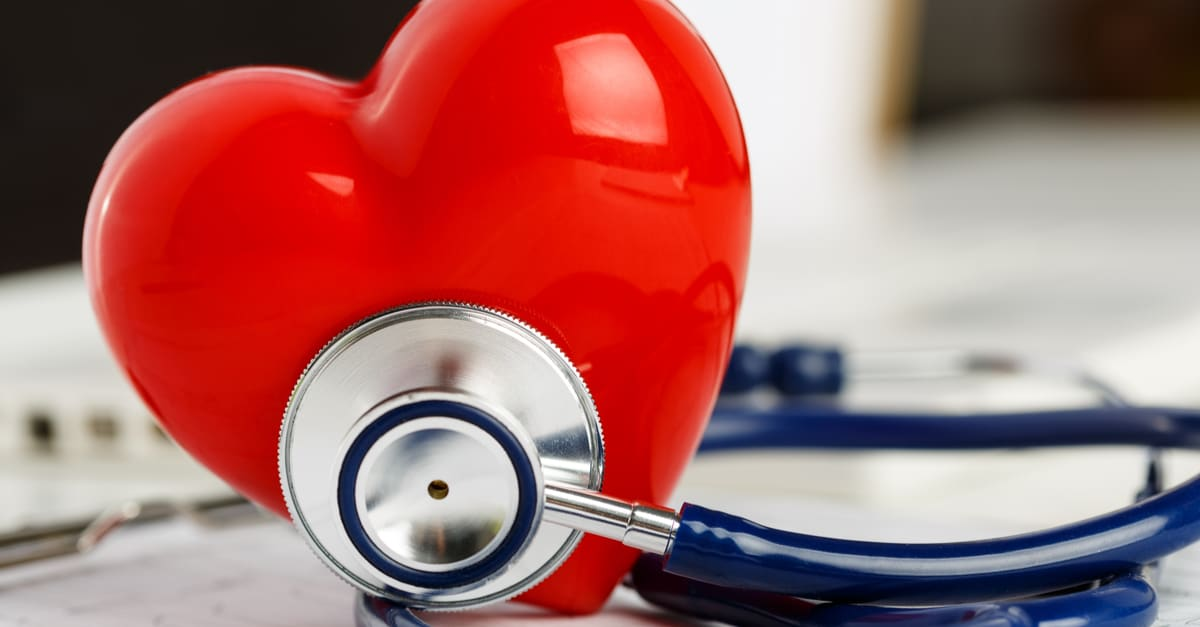 Medical stethoscope and red toy heart lying on cardiogram chart closeup.