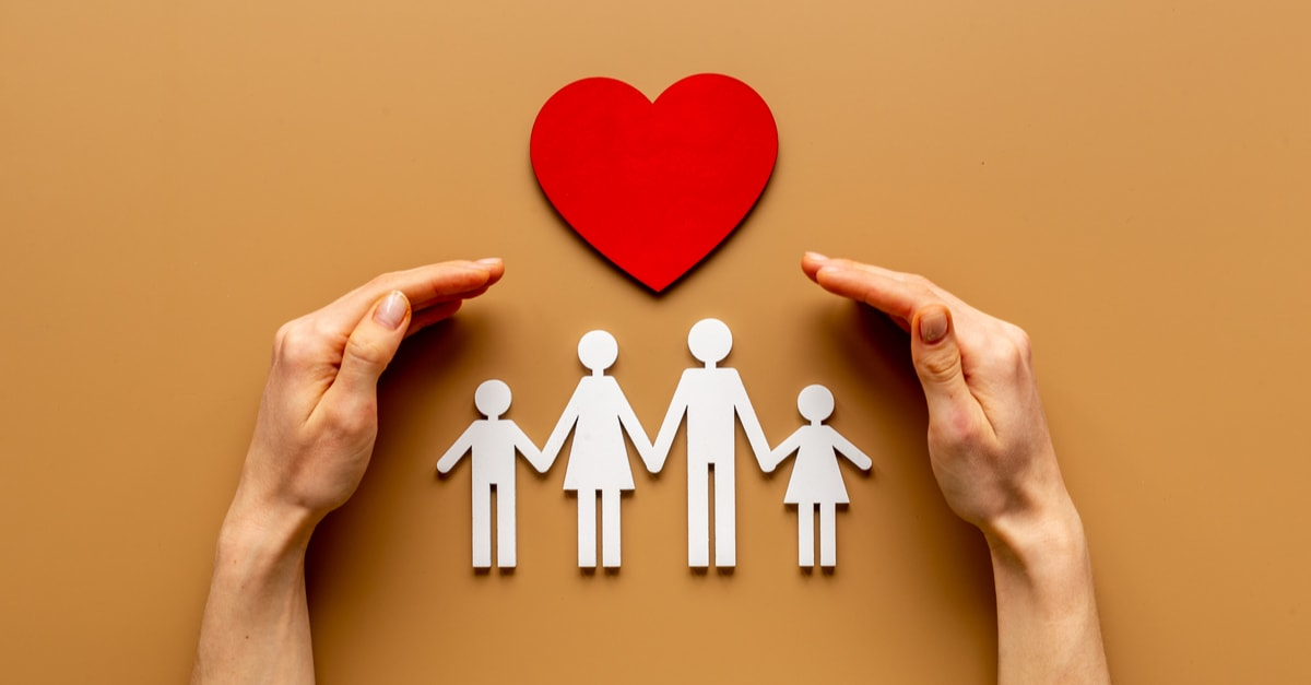 Seguro de vida Hands holding family figure. Life and health insurance concept.