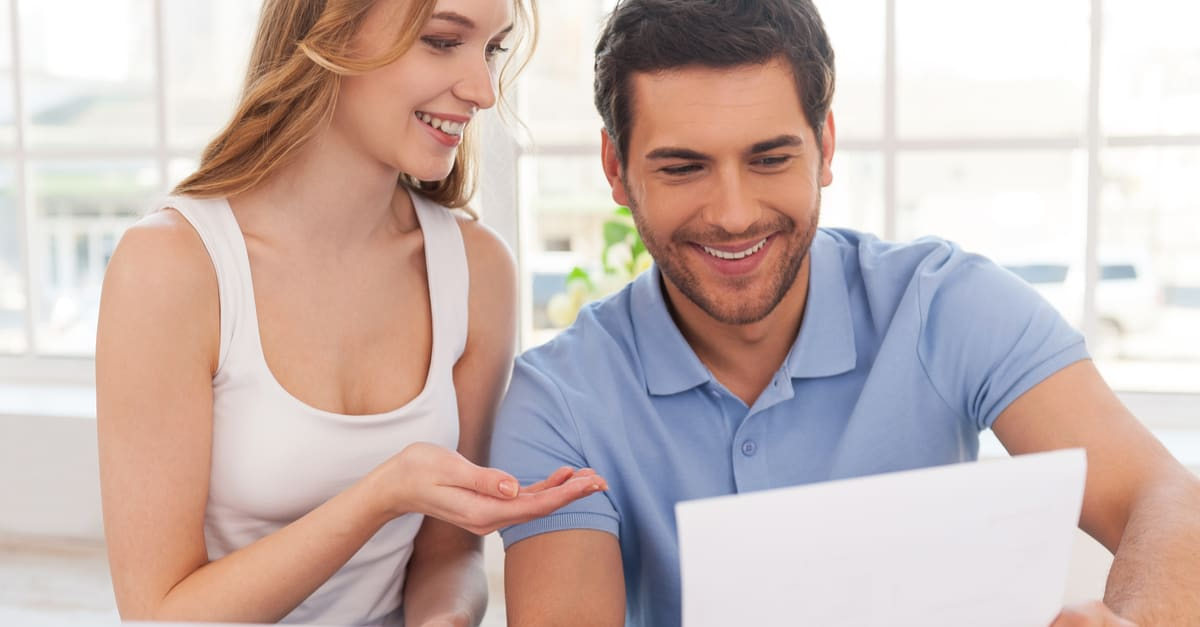 Couple examining documents. Cheerful young couple examining documents while sitting close to each other at their apartment