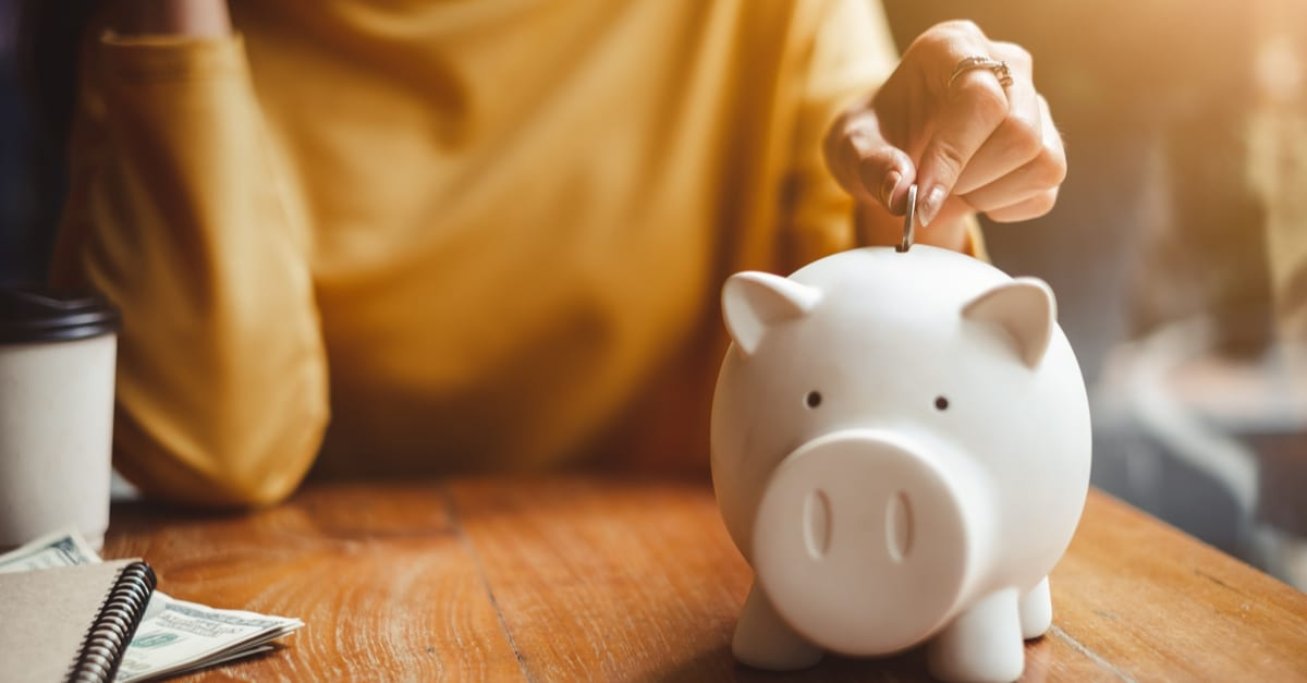 Ahorrar dinero woman hand putting money coin into piggy for saving money wealth and financial concept.