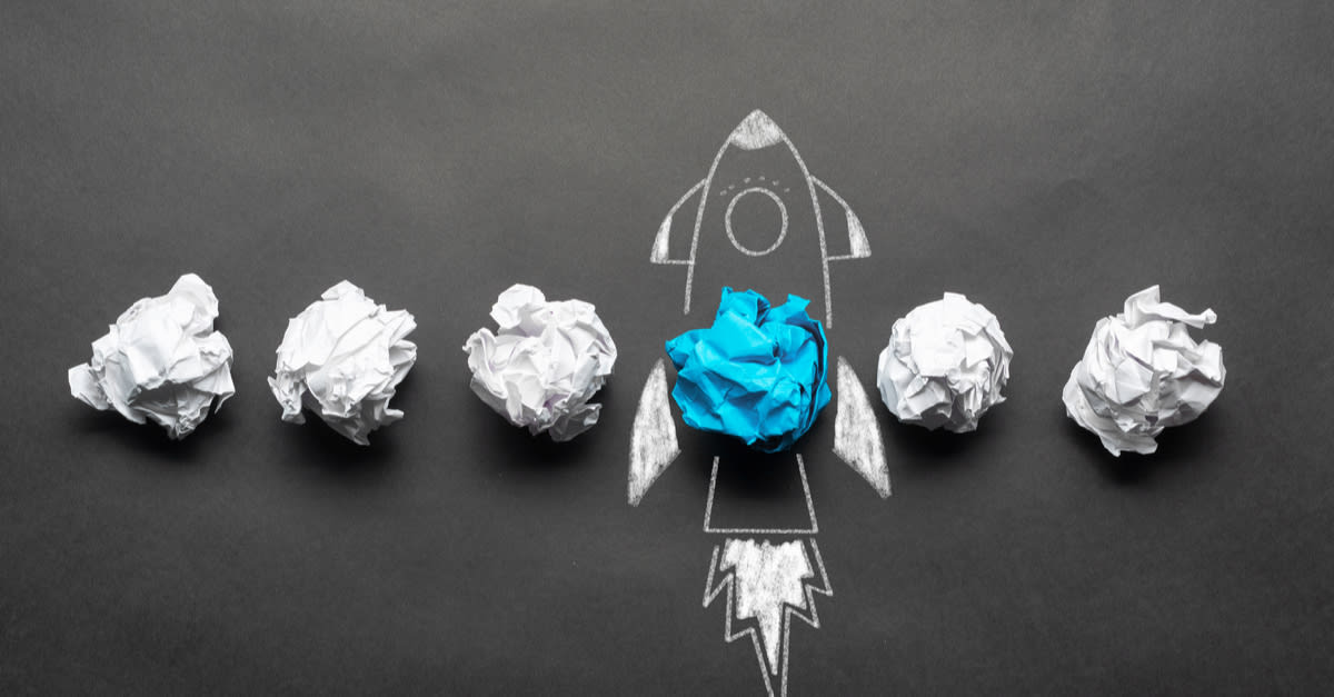 Rocket sketch drawing with crumpled blue paper ball on chalkboard. Successful business startup.
