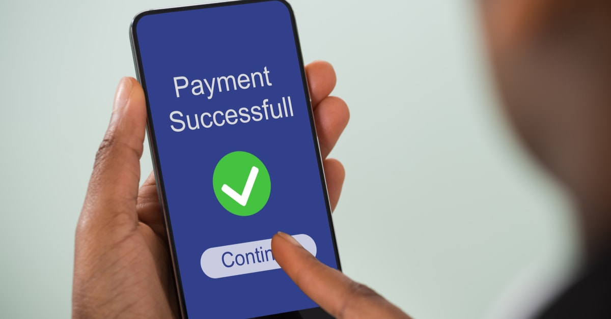 Close-up Of Persons Hand Showing Payment Successful Message On Mobilephone Screen