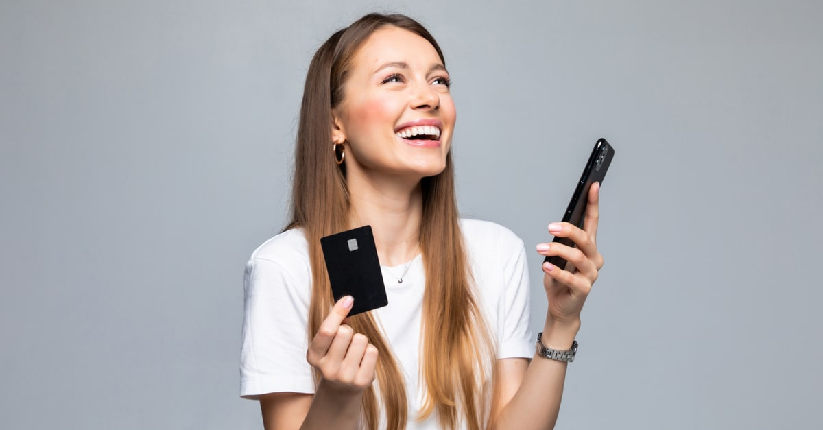 tarjeta de crédito Portrait of a smiling woman holding credit card and mobile phone while looking at camera over white background