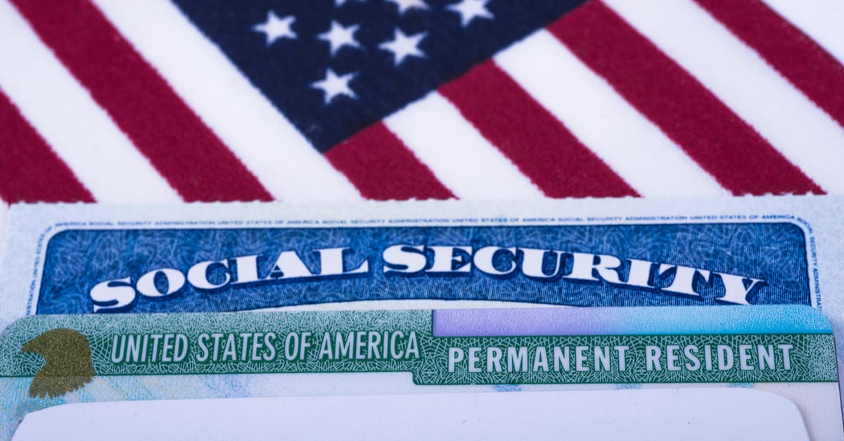 United states of America Permanent Resident (Green card) and Social security number (SSN) cards on USA Flag background.