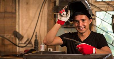 Trabajador masculino apoyado en un marco metálico con soldador en la mano