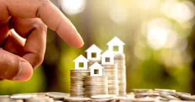 Las monedas están apiladas en cinco filas y encima hay una casa de papel blanco. Las manos de los hombres están tocando suavemente, el concepto de ahorrar dinero y crecer financieramente.