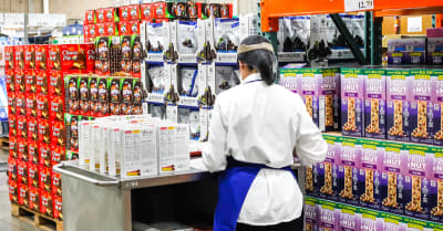 A view of a female employee standing at her kiosk offering samples to customers at a local Costco