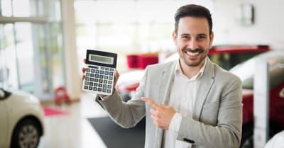 Hombre mostrando calculadora con el Precio de auto