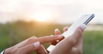 mano usando el teléfono al aire libre al atardecer