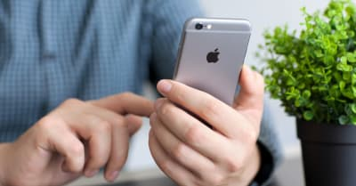 Man holding in the hand a new iPhone 6 Space Gray. iPhone 6 was created and developed by the Apple inc