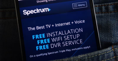Spectrum website displayed on smartphone hidden in jeans pocket