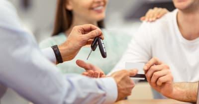 Una pareja joven sonríe mientras compra un auto, el trabajador de mediana edad de un show de motor está dando llaves, de cerca